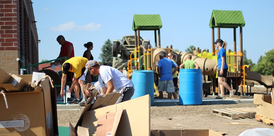 View across piles of cardboard boxes of volunteers building a playground.