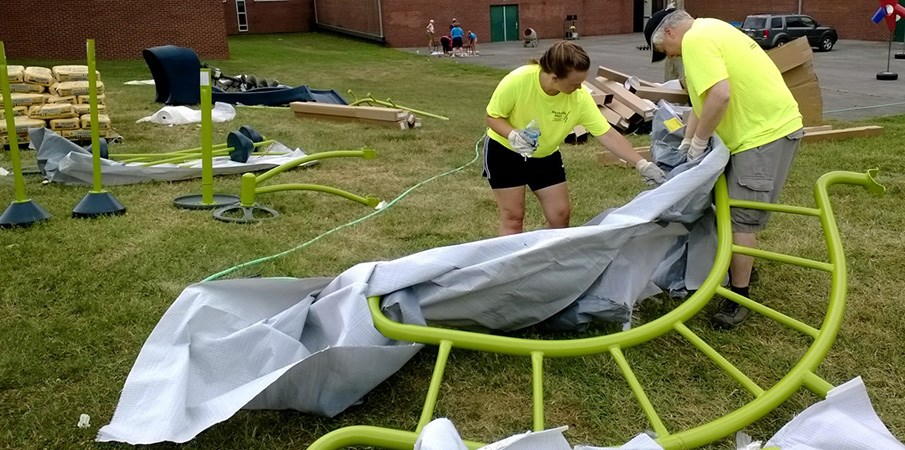 Volunteers unpacking and laying out playground equipment for a Playground Build.