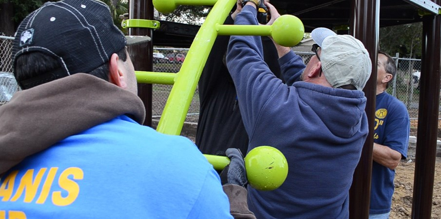 Volunteers attaching Lollipop Climber to playground decking.