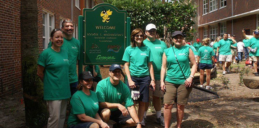 Volunteer playground builders stand next to a welcome sign to a new park.