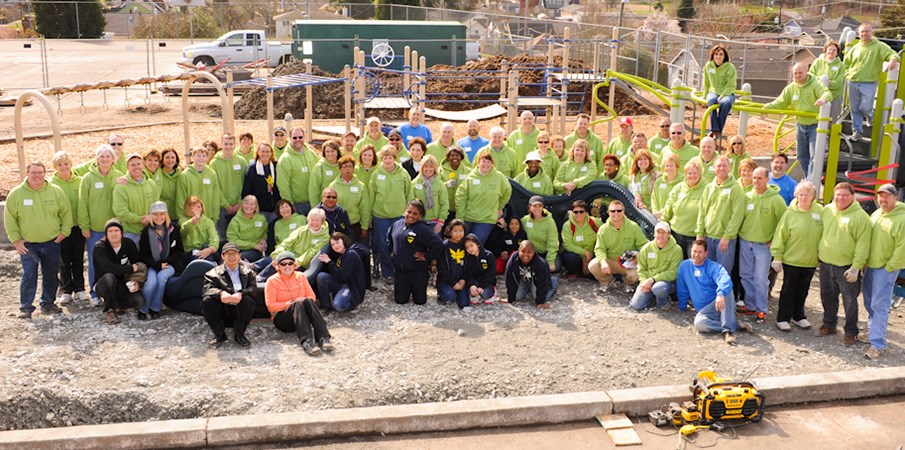 Volunteer playground builders take a  group photo at the build site.