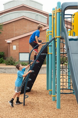 Side view of the Arcade Climber with two boys aged 5 to 12 years scaling the arched, steel climbing ladder to a PlayBooster® deck.