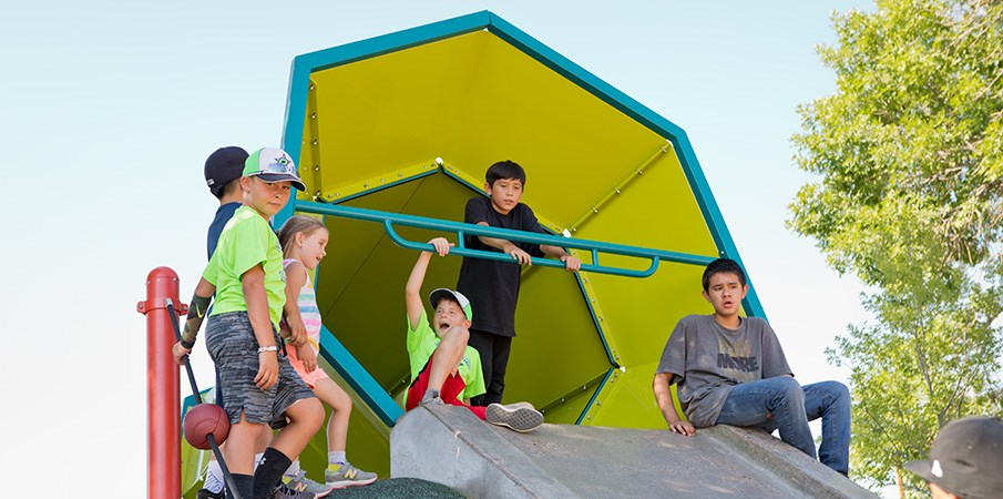 A group of boys sit at the top of a concrete slide.