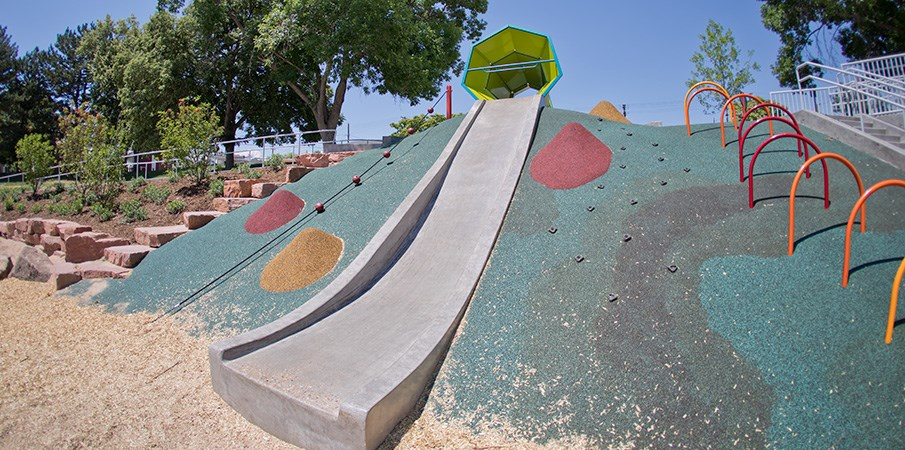 A concrete playground slide and climbers incorporated into the side of a PebbleFlex covered hill.