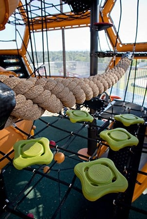 A large braided rope bridge above a cargo net with square pod steppers.