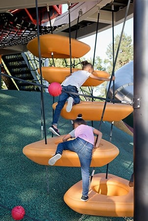 Two girls climb up vertically suspended large O-Zone climbers.
