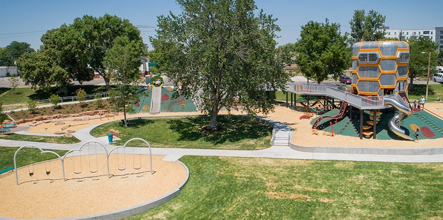 Full view of the Paco Sanchez custom inclusive playground microphone tower and swing set area.