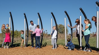 Parents and children playing on a set up Rhapsody Vibra Chimes.