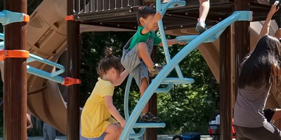 "A group of kids ages 5 to 12 ascending the curved stairway of the Dot-to-Dot Climber to the top of the 96"" PlayBooster® deck."