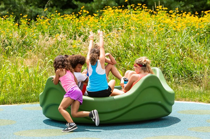 A group of kids gathered on the freestanding OmniSpin Spinner engaged in spinning, motion and fun.