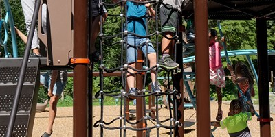 "Kids ascending the cable net of the Chimney Climb Across™ with a 24"" Deck Difference that attaches a 72"" PlayBooster® deck to a 96"" deck."