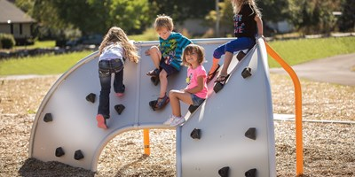Mobius Climber 3-Panel shown with boys and girls climbing. Tangerine orange posts provide supports.