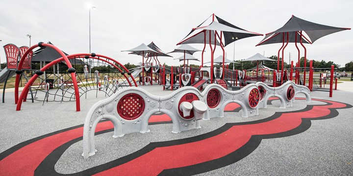 A full view of the playground at Jonesboro Miracle League Park with sensory panel learning wall in foreground.