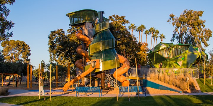 A full view of the three main playground structures shaped like local trees at Pioneer Park.