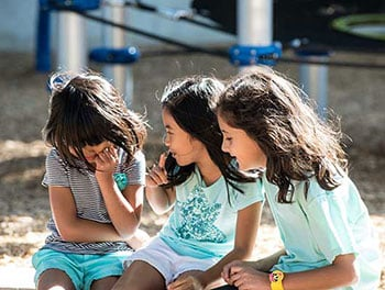 Group of girls taking a break and enjoying deep conversation on the playground
