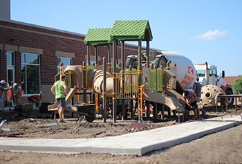 Workers shown installing a PlayShaper play system at a school. Playground has green roofs to provide shade, a crawl tunnel and poly slide.