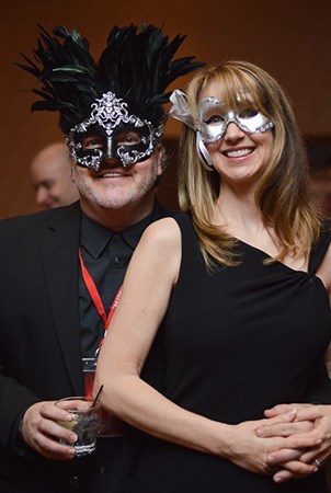 A man and woman smile for the camera while dressed up and wearing masked ball face masks.