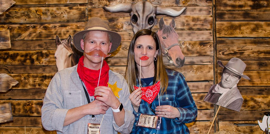 A man and women hold up a fake mustache and lips to their face while standing in front distressed barn wood at a holiday party.