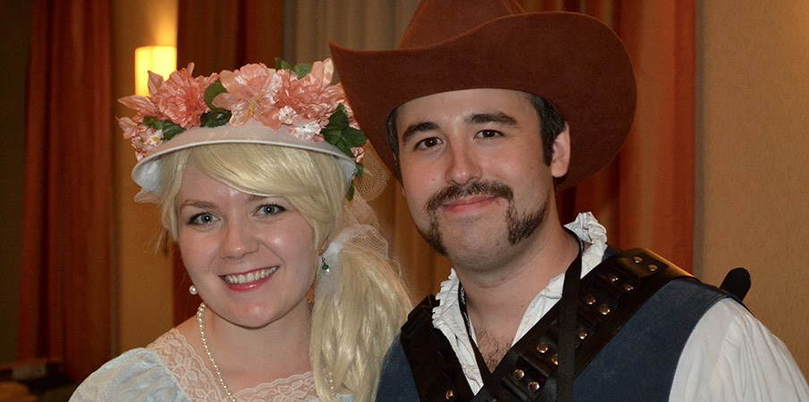 A man and women smile in old western clothing at a holiday party.