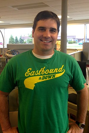 Landscape Structures Brock Suska smiles for the camera while wearing a Eastbound and Down t-shirt.
