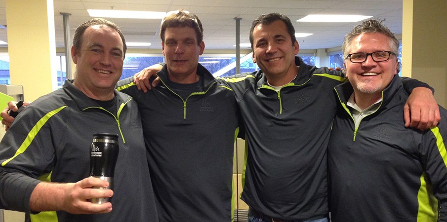 President Pat Faust stands with three other Landscape Structures employees in matching sweatshirts.