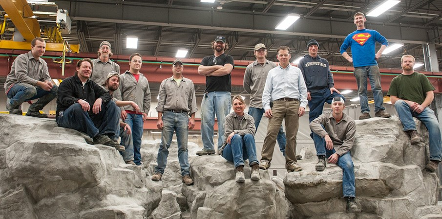 The concrete group at Landscape Structures stand and sit on two rock climbers inside a manufacturing building.