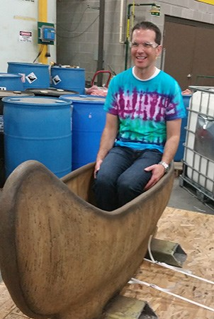 Vice President of sales David Smith smiles while sitting in a glass fiber reinforced concrete canoe in the manufacturing building.