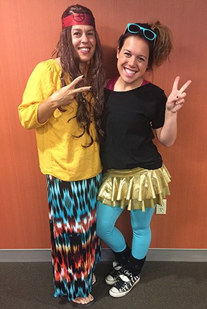 Two women give peace signs to the camera while wearing 70s and 80s on Decades Day.