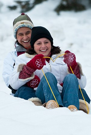 Two people smile as they sled down a snowy hill.