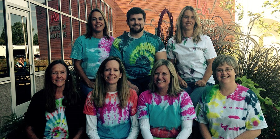 The human resource team at Landscape Structures pose for the camera while wearing home made tie dye t-shirts.