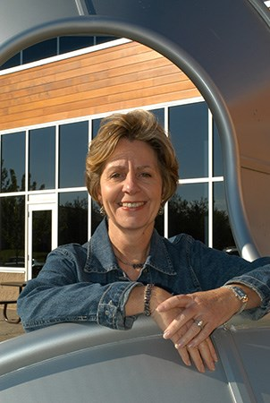Barb King co founder of Landscape Structures posing for a photo while leaning on a Mobius Climber.