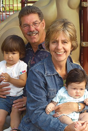 Landscape Structure founders Steve and Barb King smile while sitting with babies on a playground.