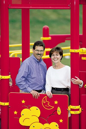 Landscape Structure founders Steve and Barb King smile while standing behind a Permaline panel on a playground.