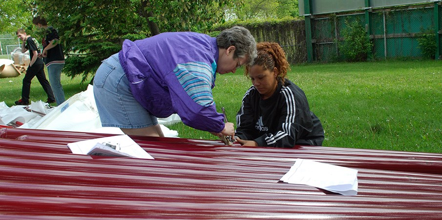 Volunteers assembling playground equipment.