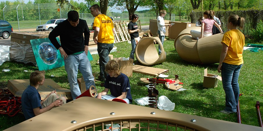 Volunteers assembling playground equipment in the grass.