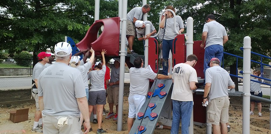 Volunteers build a playground slide.