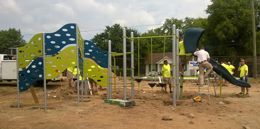 Community volunteers constructing a PlayBooster playground with slide and 4-panel Cascade Climber.