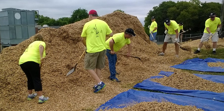 Volunteers adding wood chips to playground surfacing area