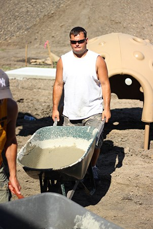 Volunteer pushing wheelbarrow with concrete at a playground building site.