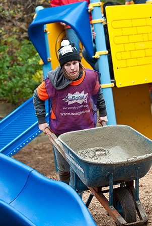 KaBOOM! volunteer pushing wheelbarrow with concrete at a playground building site.