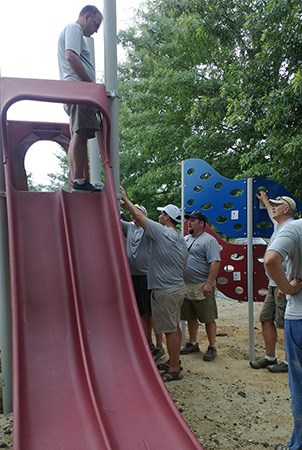 Volunteers attaching a Cascade Climber to a playground.