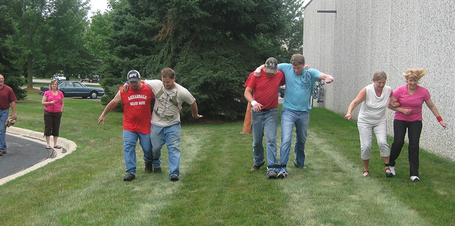 Landscape Structure employees race in a three legged race outside.