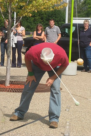 Landscape Structures employee playing a game where he has to knock a water bottle over with a tennis ball dangling from tights attached to his head.
