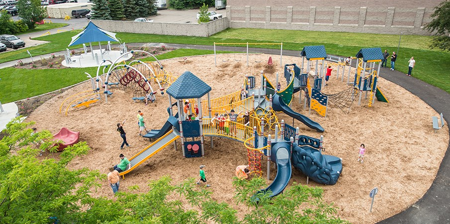Elevated view of children playing on Evos and PlayBooster playground sets.