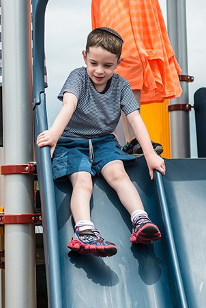 Young boy sliding down a PlayBooster Double Swoosh Slide.