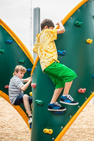 Kids climbing on a PlayBooster curved playground climber with foot and hand holds.