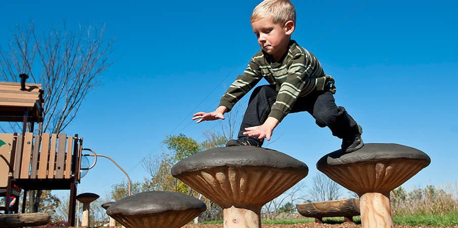 A young boy steps from one mushroom stepper to the next.