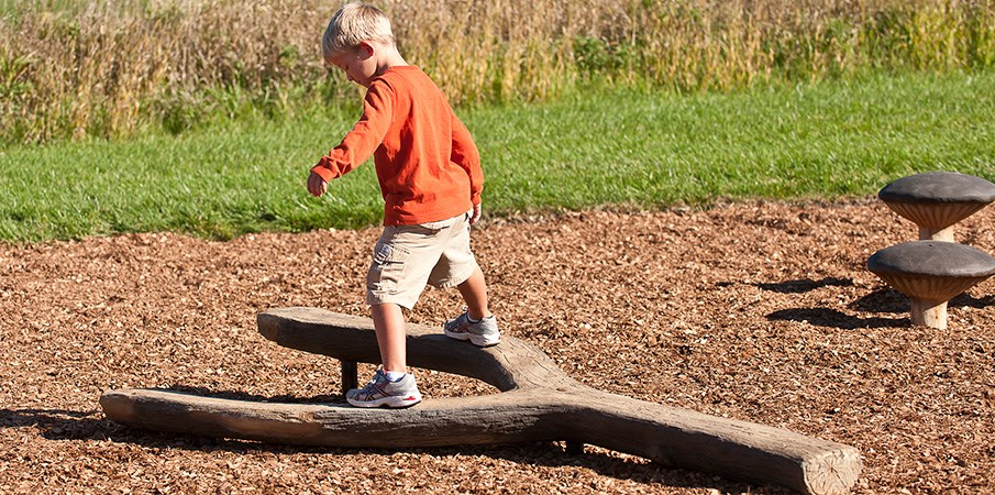 Young boy walking on log balance beam.