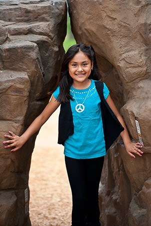 A young girl stands between the Pinnacle and pointe rock climber