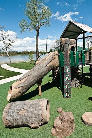Nature themed playground with log slide and tunnels.